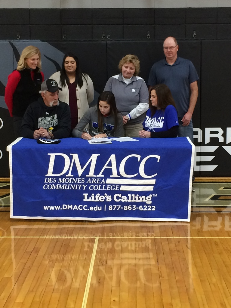 Chloe signs on with DMACC for volleyball with mom, dad, and coaches looking on.